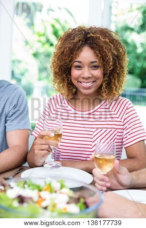 Portrait of happy young woman drinking wine with friends at home