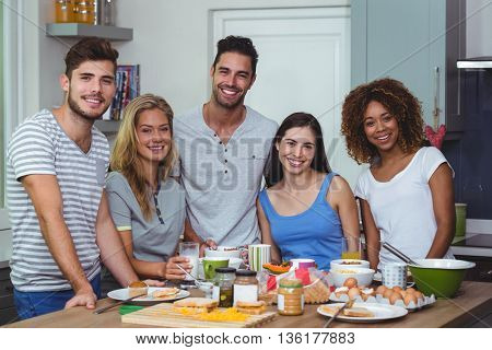 Portrait of cheerful young friends standing at table in kitchen