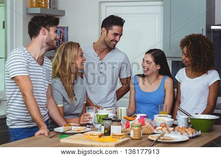 Happy friends discussing while having breakfast at table in kitchen