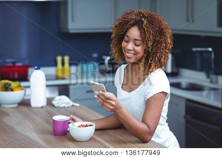 Happy woman using smartphone with food at table