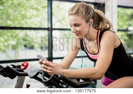 Woman listening music and text messaging on smartphone while sitting on exercise bike