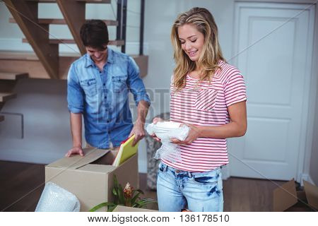 Smiling woman unpacking bowls from box with man at home