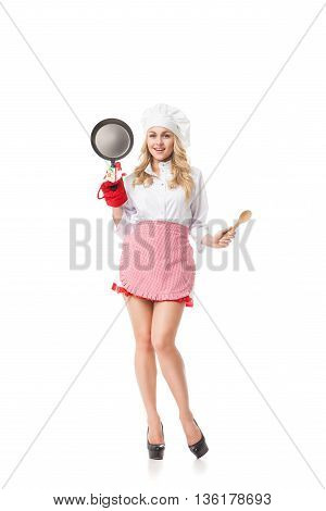 Portrait of smiling waitress with pan and spoon.Studio shot