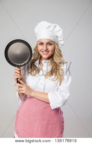 Studio shot of beautiful smiling woman in apron and hat showing frying pan.Isolated.