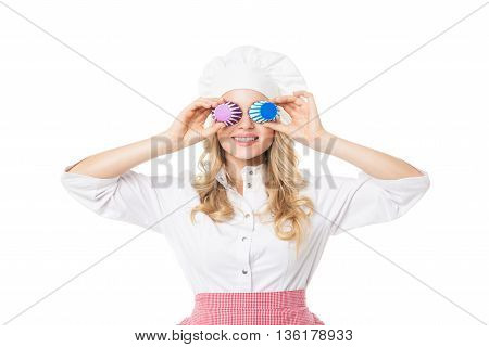 Portrait of smiling blonde woman covering eyes with cupcake baking forms.Studio shot.Isolated.