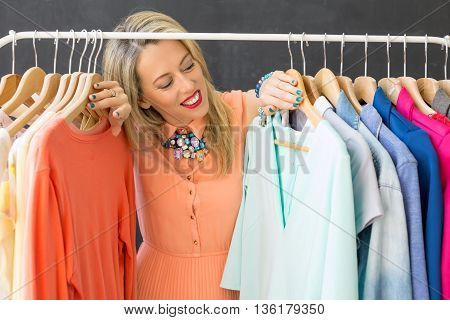 Beautiful woman looking at clothes on the cloathing rack