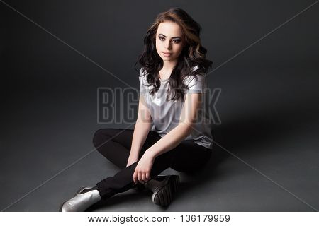 Portrait of beautiful young woman sitting on floor with windy hair