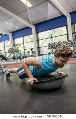 Man working out with bosu ball at gym