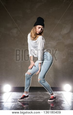 Portrait of blonde model in hat and casual clothes posing against of lights and brown urban wall
