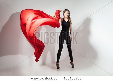 Young girl in black with waving red cloth on white background