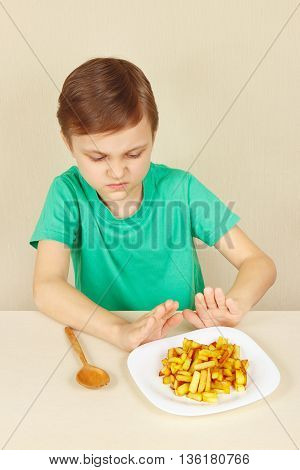 Little boy does not want to eat a french fries