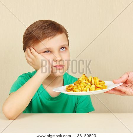Little cute boy refuses to eat a fried potatoes