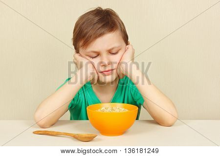Little displeased boy does not want to eat a cereal poster