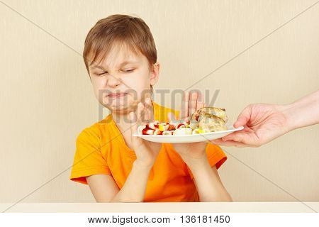Little discontented boy refuses to eat a pasta with rissole