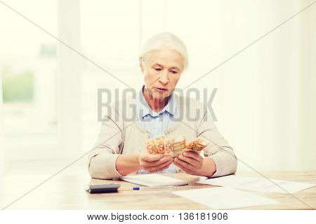 business, savings, annuity insurance, age and people concept - senior woman with calculator and bills counting euro money at home