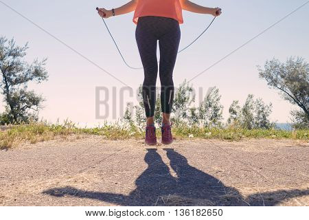Girl In Sportswear And Sneakers Jumping With A Skipping Rope On In The Summer Of The Sea Background