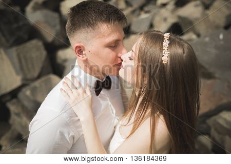 Wedding couple in love kissing and hugging near rocks on beautiful landscape.