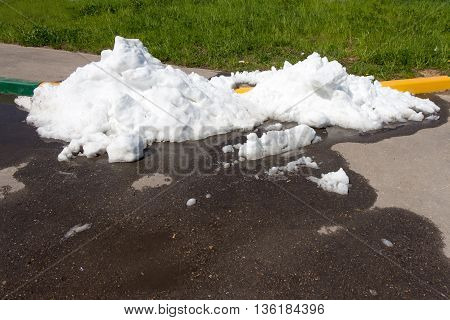 A large pile of dirty snow (ice) lies in the summer on the road and melts