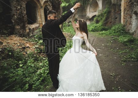 Amazing happy gentle stylish beautiful romantic caucasian couple on the background ancient baroque castle.