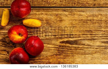 Fresh nectarine with water drops on wood table top view copy space