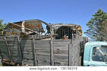Old truck with wooden box loaded with a wrecked car ready to be crunched.