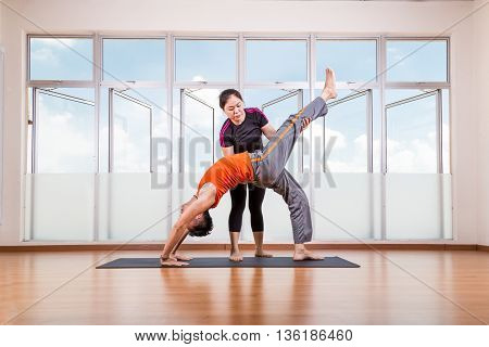 Yoga Instructor Assisting Student Perform Backbend Or Chakrasana Pose