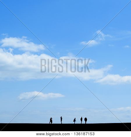 Silhouette of people walk on The Cobb in Lyme Regis Dorset