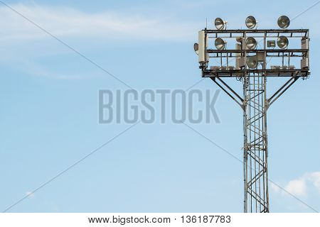 High spotlights lighting tower at an sport arena stadium with blue sky background