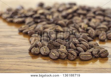 Broun coffee beans isolated on brown wooden texture background shallow depth of field