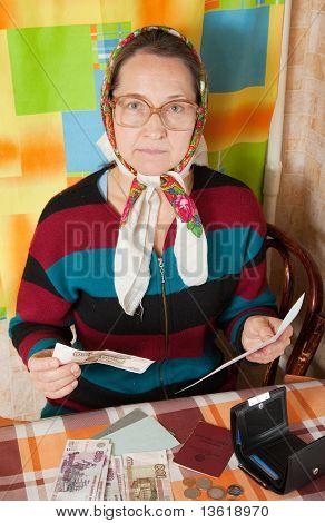 Sad Senior Woman With Bill And Money