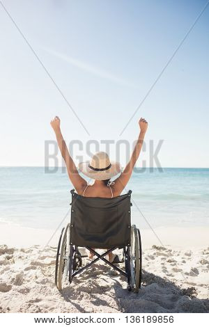 Wheelchair woman sitting with arms up on the beach