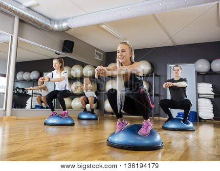 Friends Doing Squatting Exercise On Bosu Ball In Gymnasium