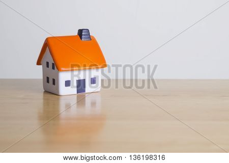 Foam house on wooden table - mortgage concept