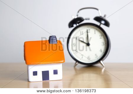 Foam house with clock in background - mortgage concept