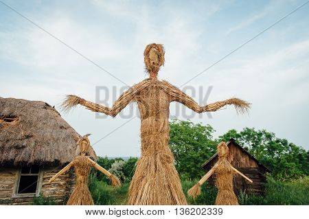 Large Handmade Doll Amulet Near A Wooden House