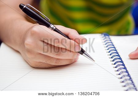 Write activity (A girl hand holds a pen and write on a book)