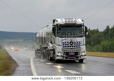 SALO, FINLAND - JUNE 17, 2016: White Mercedes-Benz Arocs 3258L tank truck of Kuljetus Auvinen hauls cement along motorway in South of Finland on a rainy day in June.