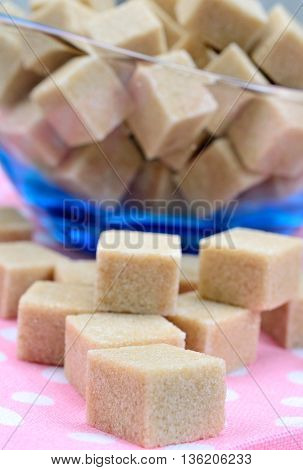 Brown sugar cubes on table close up
