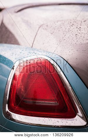 Detail on the rear light of a car on a rainy day.