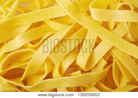 Surface covered with the raw fresh fettuccine ribbon pasta as a backdrop composition