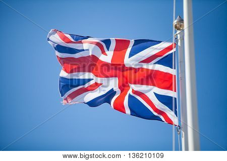Color image of the United Kingdom flag on cloudy background.