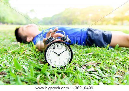 Black Alarm Clock And Sleeping Boy In The Park