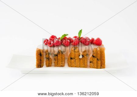 Christmas fruit cake with red raspberries on white background