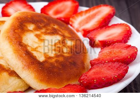 fritters on a plate with strawberries on wooden background.