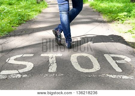 Stop sign painted on the road and female legs next to the sign.