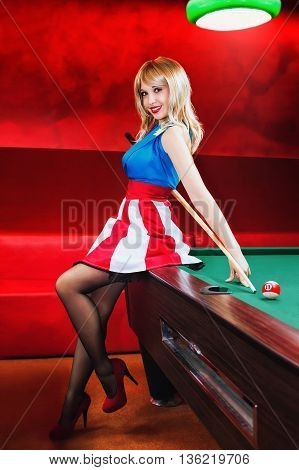 Pin-up and billiards. Blonde girl in pin-up style plays to the pool table.