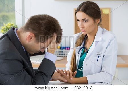 Female medicine doctor holding business man hand for encouragement telling him bad news. Immediate relative loss stress headache and medical service concept