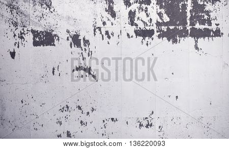 Grungy white painted concrete wall, with white paint peeling off in some areas.