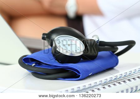 Close up view of manometer laying on working table. Hospital workspace. Healthcare medical service treatment hypotonia or hypertension concept. Female doctor operating on background. Copyspace