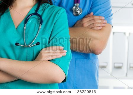 Close up view of two doctors standing with their arms crossed on chest ready to work. Health care medical and teamwork concept.
